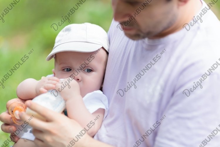 Father feeding his baby from the bottle example image 1