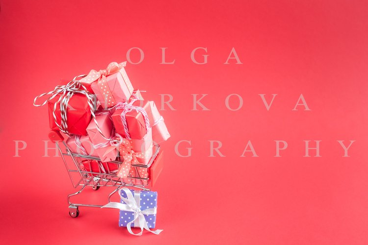Trolley shopping cart filled with paper wrapped gift boxes example image 1