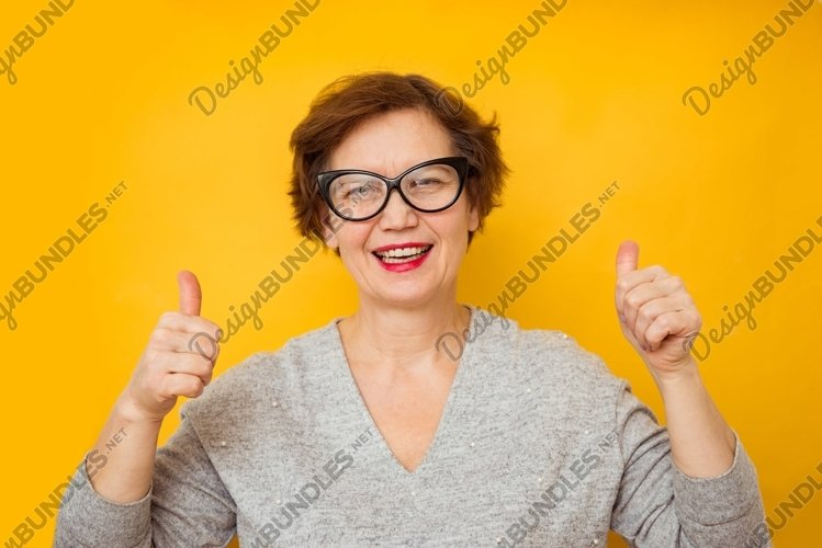 Portrait of elderly woman showing thumbs up example image 1