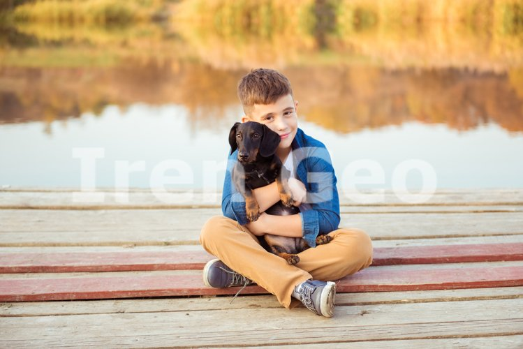 Young boy hugging black dog outdoors example image 1