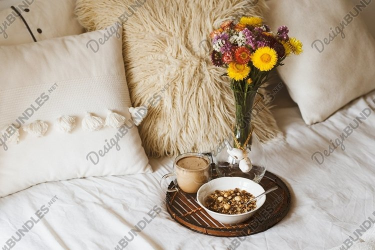 Breakfast in bed with coffee cup and granola on tray.