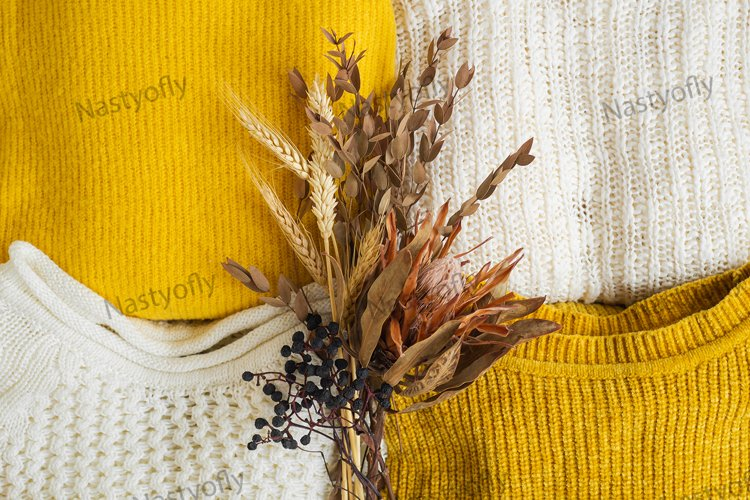 Pile of knitted clothes yellow white color with dried flower