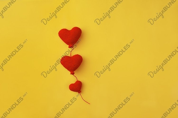 three knitted red heart-shaped balloons on yellow background example image 1