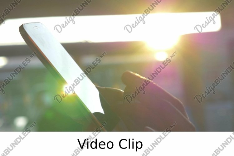 Video: Female hands typing on cell against evening sunshine example image 1