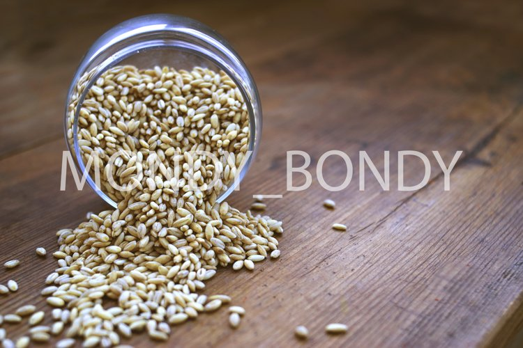 Pearl barley in a jar is scattered on a wooden table