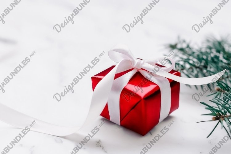 New Year and Christmas present in red wrap with white ribbon example image 1