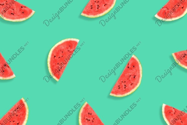 Flat lay of watermelon half slices on mint background.