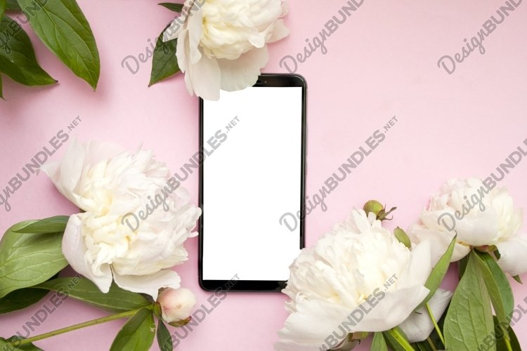 Phone and white peonies on a pink background.
