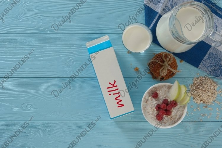 Milk in a cardboard box and cookies on a wooden background example image 1