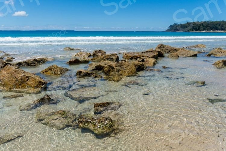 Tropical paradise beach with rocks in the water example image 1
