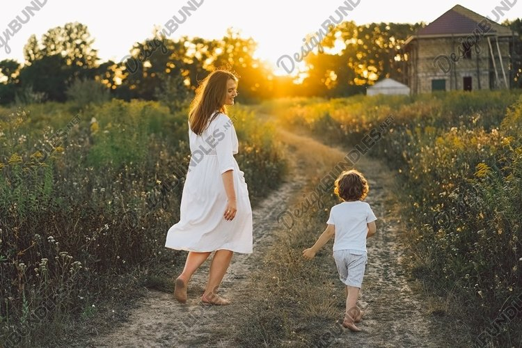 Woman playing with her child on the field during sunset. example image 1