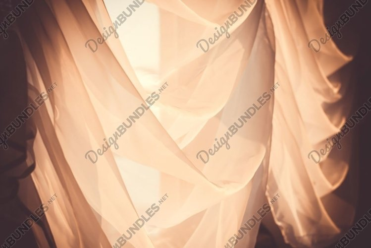 Elegant, thin transparent curtain on the window, by sunlight
