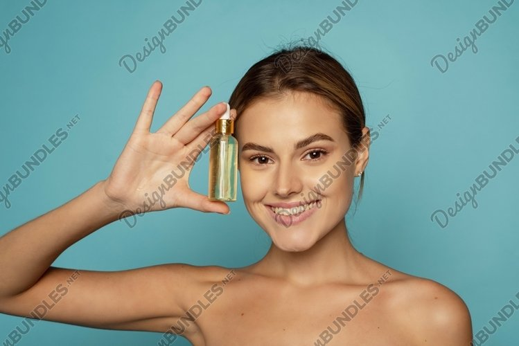 A beautiful young woman moisturizes her skin with a serum.