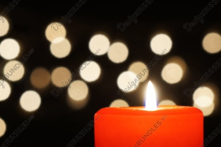 red candle with christmas lights bokeh