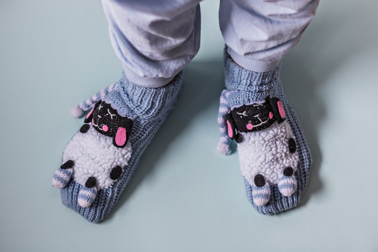 Legs of a girl in funny blue socks with lambs. Cozy slippers example image 1