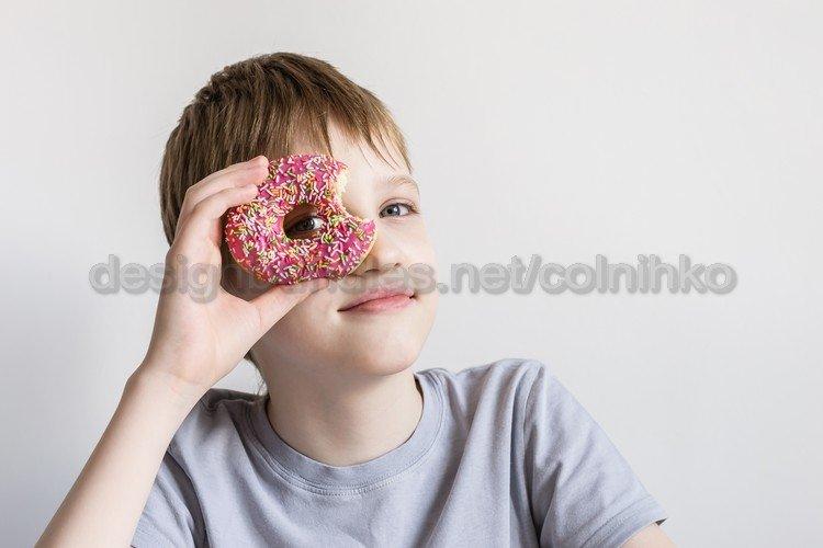Teen boy looks into hole of bitten donut