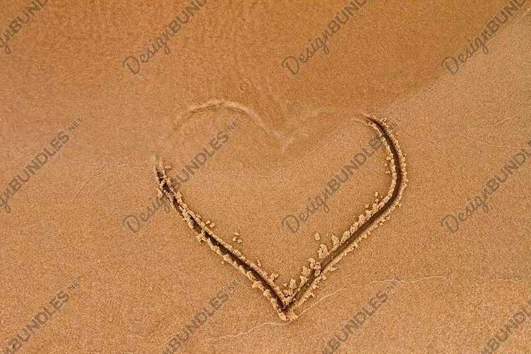 Hand-drawn heart shape on wet yellow sand, covered by wave example image 1