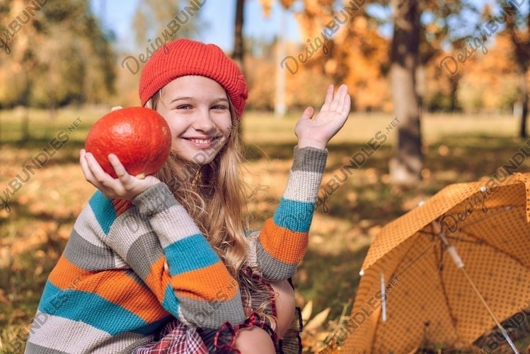autumn portrait of young girl with pumpkin