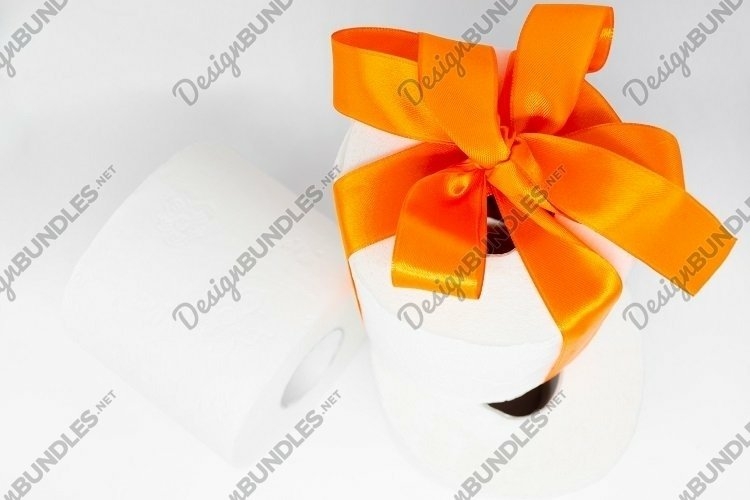 Several rolls of white toilet paper. Orange bow. Copy space