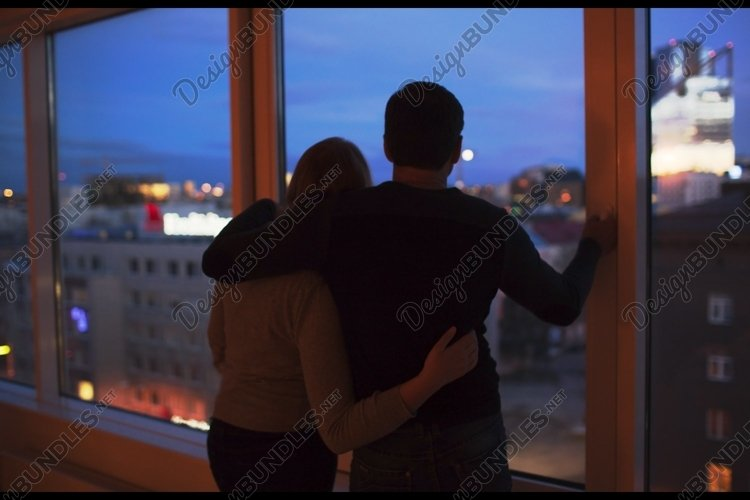 Couple embracing and looking at evening city together example image 1