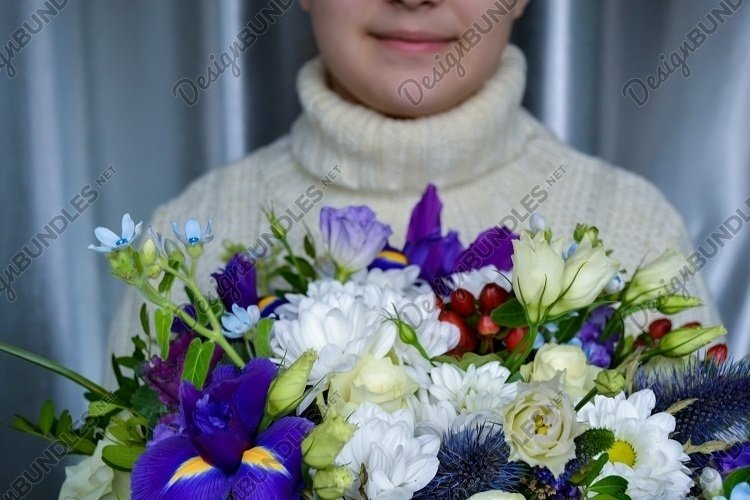 Blue and white bouquet of flowers holds someone smiling