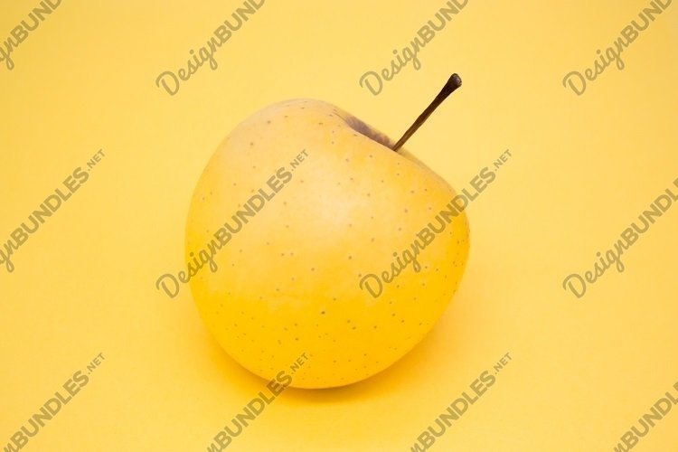 Yellow apple on yellow background example image 1