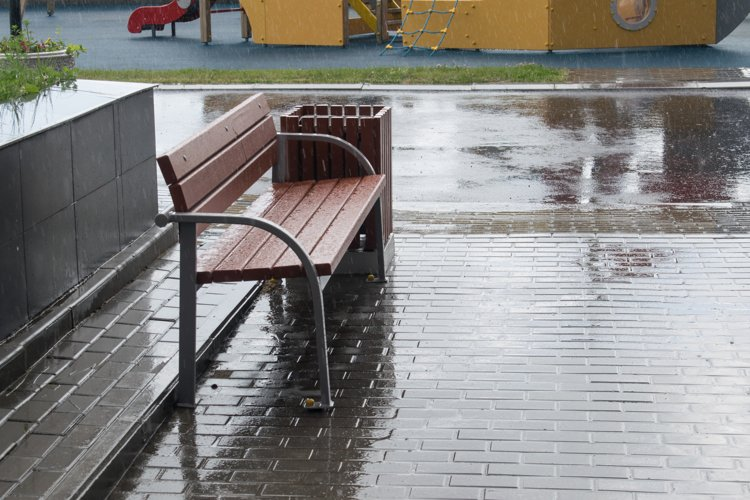 bench shop stands near the house in the rain