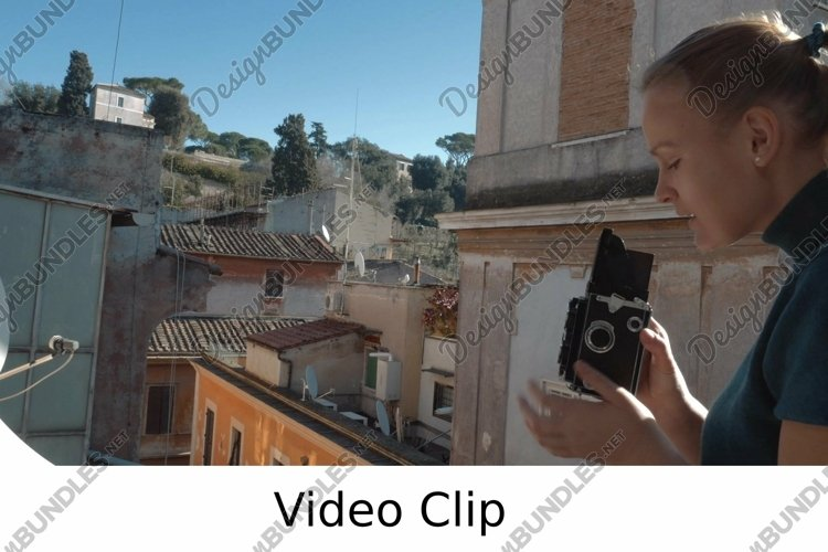 Video: Woman with retro camera on the balcony example image 1