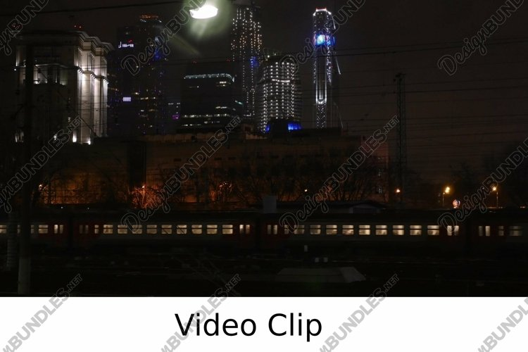 Video: Passenger train passing through the city at night example image 1