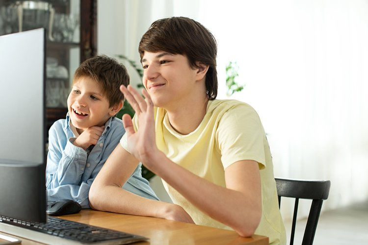 Smiling boy and teenager chatting online video call example image 1