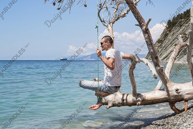 A guy is sitting on a swing made of a fallen tree. 2pcs example image 1