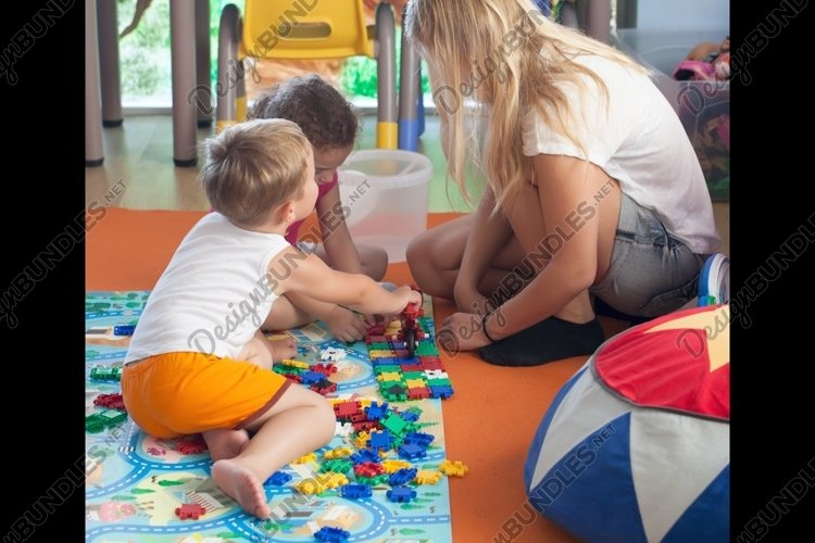 Doing puzzle with tutor in nursery example image 1