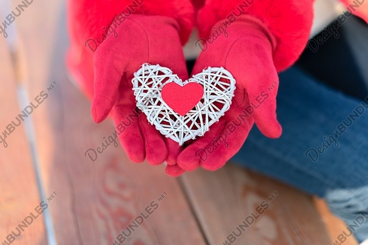 Small red heart on white rattan heart in woman hand example image 1