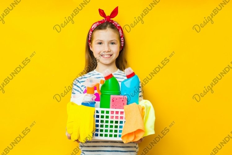Smiling child girl holding basket with detergents