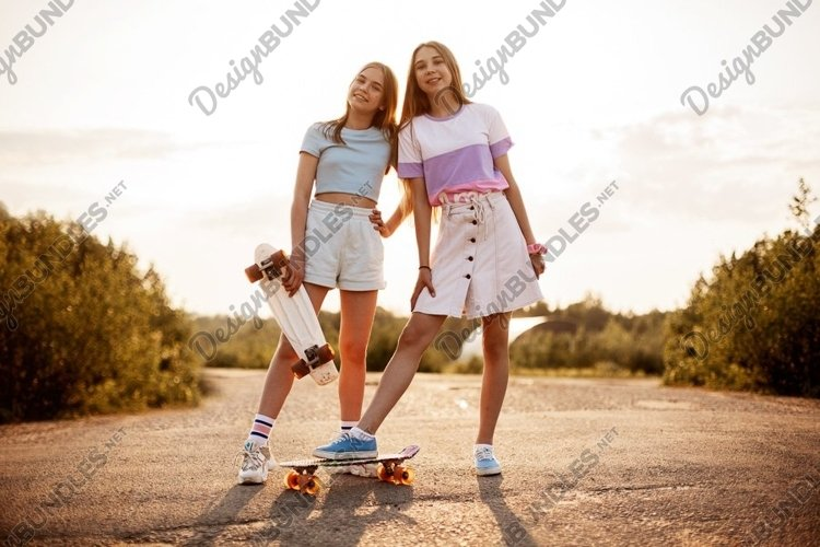 Two blond teenage girls in hipster clothes with a skateboard example image 1