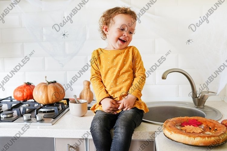 Cute girl is sitting on the table near halloween pumpkin example image 1