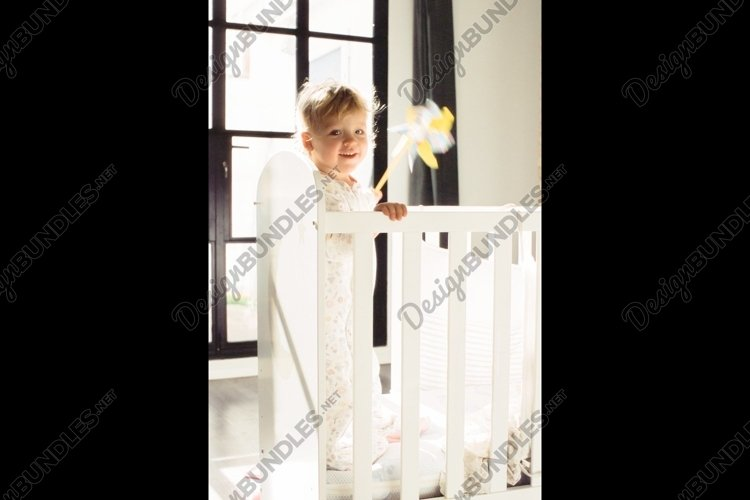 Happy child with toy in the crib example image 1