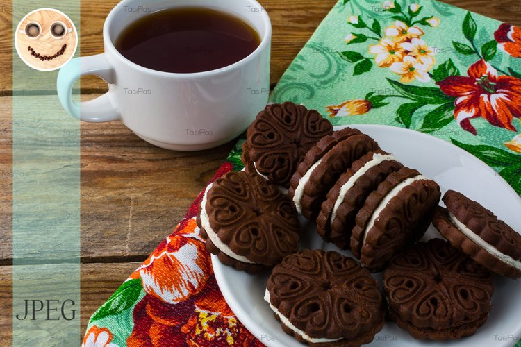 Chocolate cookies sandviches and cup of tea