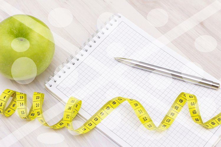 green apple, a measuring tape and a notebook for writing on example image 1
