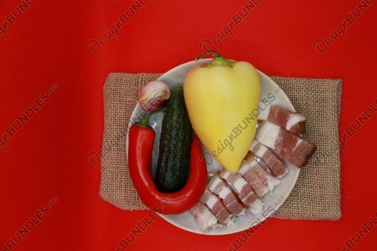 pieces of lard with vegetables on a plate example image 1