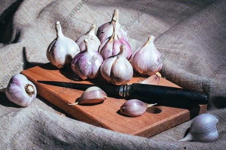 Garlic slices and old knife on a wooden cutting board example image 1