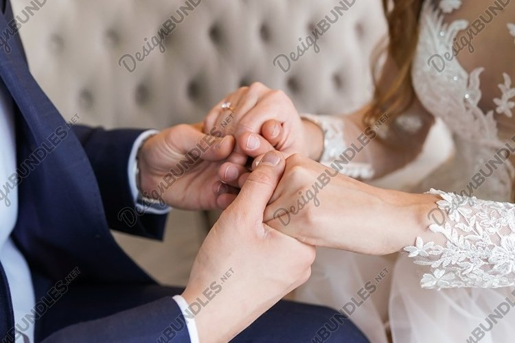 Bride and groom gently holding hands each other example image 1