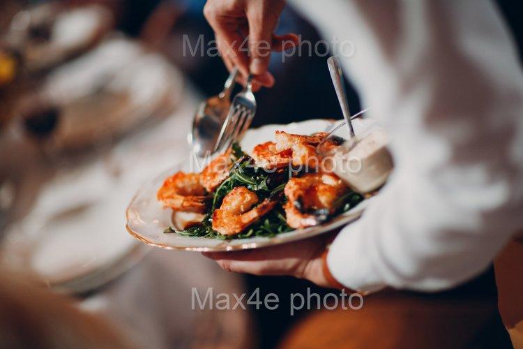 Waiter serves shrimp with arugula