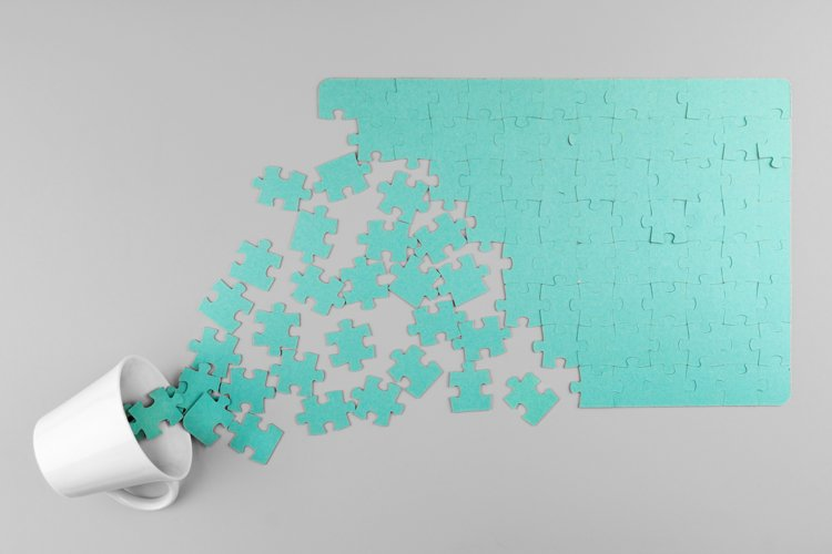 a blue puzzle spills out of a coffee Cup