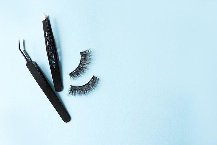 False eye lashes, black tweezers on blue background example image 1