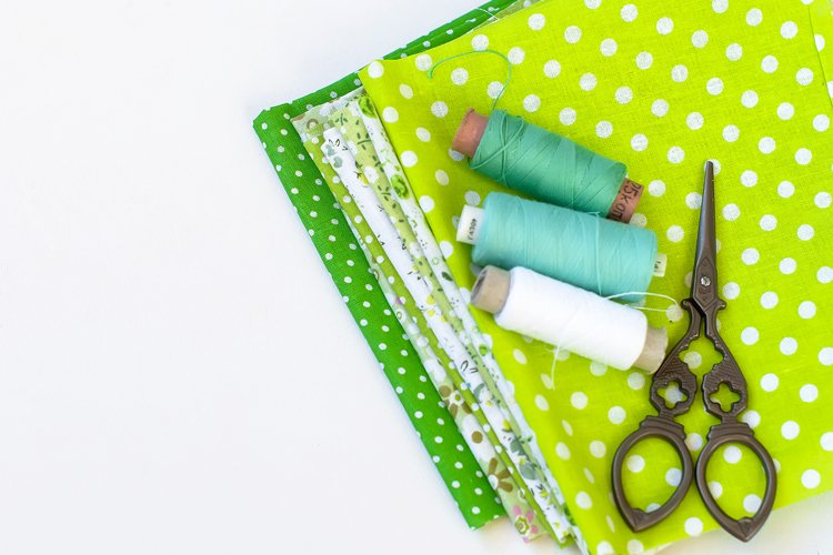 Sewing set with fabric, spools of thread, scissors and glass