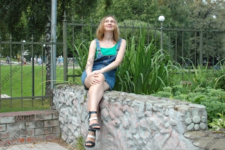 A girl is sitting on a stone bench example image 1