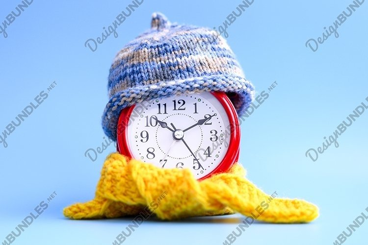 alarm clock in knitted hat and scarf. winter time concept example image 1