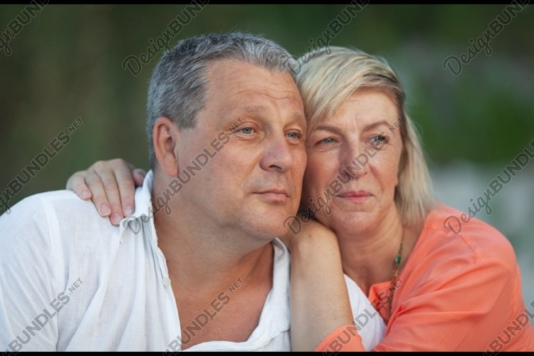A portrait of a smiling middle aged couple looking into example image 1