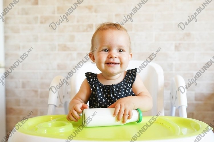 Smilling baby holding bottle of milk in sunny modern kitchen example image 1